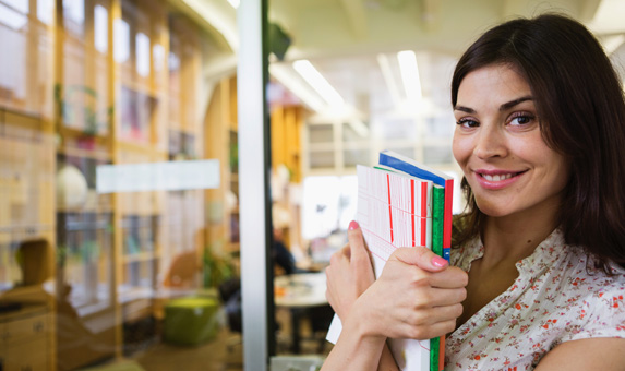 Portrait of smiling young businesswoman with books in office